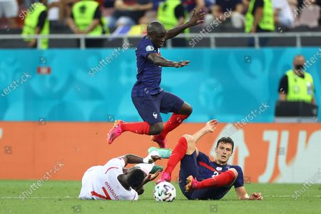 Switzerland's Breel Embolo, left, is challenged by France's Benjamin Pavard, right, and France's N'Golo Kante during the Euro 2020 soccer championship round of 16 match between France and Switzerland at the National Arena stadium, in Bucharest, Romania