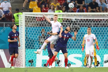 Switzerland's Nico Elvedi, top, heads the ball past France's Olivier Giroud during the Euro 2020 soccer championship round of 16 match between France and Switzerland at the National Arena stadium, in Bucharest, Romania