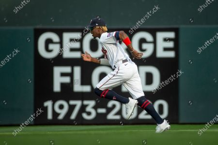 Minnesota Twins' Nick Gordon runs in front of a sign commemorating George Floyd before a baseball game with the Cleveland Indians, in Minneapolis. Earlier in the day, Floyd's murderer, Derek Chauvin, was sentenced to prison. The Twins won 8-7