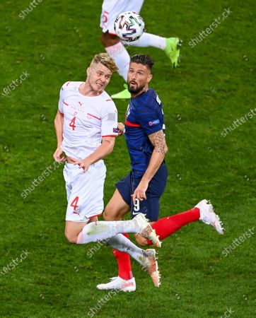 Switzerland's Nico Elvedi, left, heads the ball away from France's Olivier Giroud during the Euro 2020 soccer championship round of 16 match between France and Switzerland at National Arena stadium, Bucharest, Romania