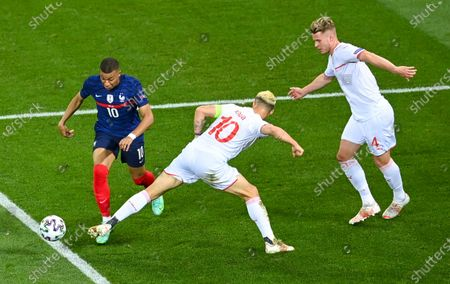 France's Kylian Mbappe, left, takes the ball past Switzerland's Granit Xhaka as Nico Elvedi, right, watches during the Euro 2020 soccer championship round of 16 match between France and Switzerland at National Arena stadium, Bucharest, Romania