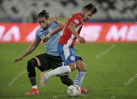 Stock Photo of Paraguay's Angel Romero, right, and Uruguay's Martin Caceres battle for the ball during a Copa America soccer match at Nilton Santos stadium in Rio de Janeiro, Brazil