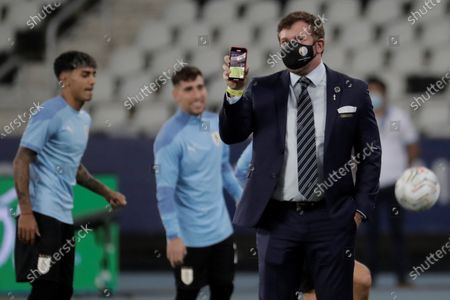 President of Conmebol Alejandro Dominguez shows his cellphone prior to the Copa America Group A soccer match between Uruguay and Paraguay at the Nilton Santos Olympic Stadium in Rio de Janeiro, Brazil, 28 June 2021.