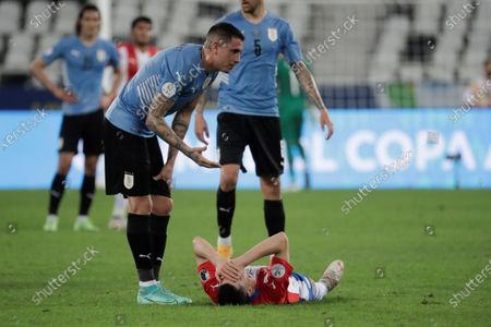 Uruguay's Jose Maria Gimenez (L) helps the injured Paraguay's Miguel Almiron during the Copa America Group A soccer match between Uruguay and Paraguay at the Nilton Santos Olympic Stadium in Rio de Janeiro, Brazil, 28 June 2021.