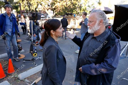 """LOS ANGELES, CA - OCTOBER 16, 2018 - Author Michael Connelly, right, talks with actress Jacqueline Obradors, left, on the film set shooting of """"Bosch"""" Season 5 in the San Fernando Valley on October 16, 2018. Obradors plays the part of Detective Renee Ballard based on Los Angeles Police (LAPD) Detective Mitzi Roberts and is the inspiration of Connelly's new character in the show. (Al Seib / Los Angeles Times)"""