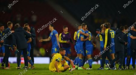 Stock Picture of A dejected Marcus Berg of Sweden slumps to the floor as the Ukraine players and staff celebrate behind him; Hampden Park, Glasgow, Scotland; EUFA European 2020 Football Championships, Round of Sixteen, Sweden versus Ukraine.