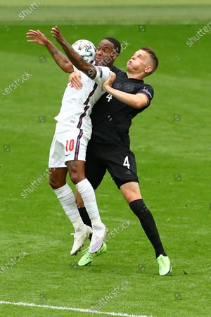 Raheem Sterling of England is challenged by Matthias Ginter of Germany.
