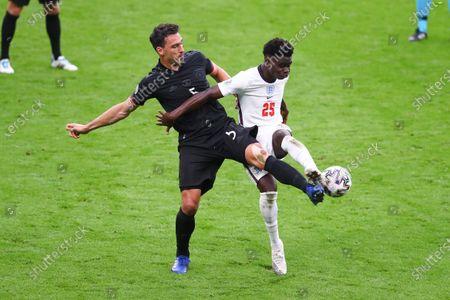 Mats Hummels of Germany challenges Bukayo Saka of England.