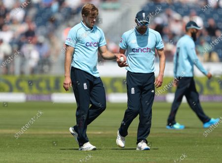 England's David Willey, left, takes the ball from teammate Mark Wood before bowling his next delivery during the first one day international cricket match between England and Sri Lanka, in Chester-le-Street, England