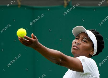Venus Williams of the US serves to Romania's Mihaela Buzarnescu during the women's singles first round match on day two of the Wimbledon Tennis Championships in London