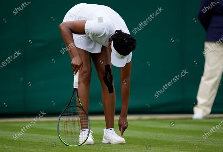 Venus Williams of the US adjusts her shoe during the women's singles first round match against Romania's Mihaela Buzarnescu on day two of the Wimbledon Tennis Championships in London