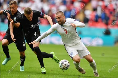 England's Luke Shaw, right, challenges for the ball with Germany's Matthias Ginter during the Euro 2020 soccer championship round of 16 match between England and Germany at Wembley Stadium in England