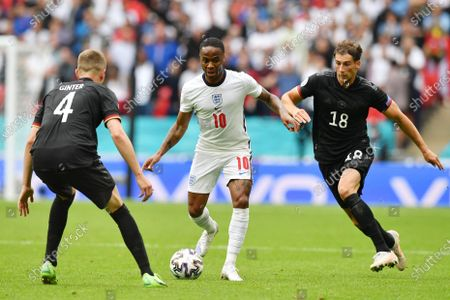 England's Raheem Sterling, centre, is challenged by Germany's Matthias Ginter, left and Leon Goretzka during the Euro 2020 soccer championship round of 16 match between England and Germany at Wembley Stadium in England