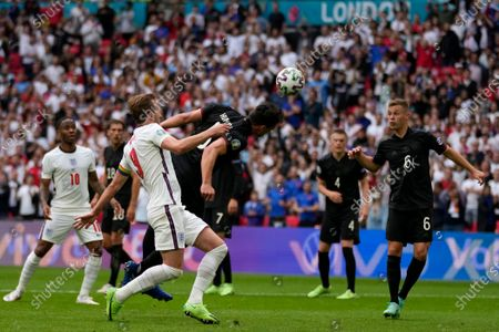 Germany's Mats Hummels, center, clears the ball away from England's Harry Kane during the Euro 2020 soccer championship round of 16 match between England and Germany at Wembley stadium in London