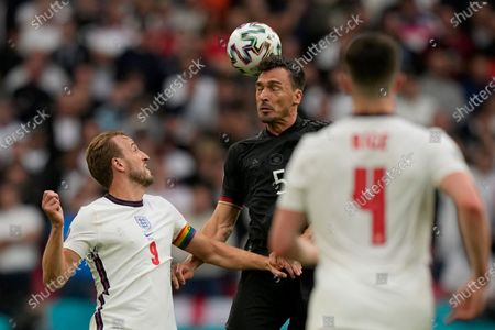 England's Harry Kane, left, watches as Germany's Mats Hummels heads the ball during the Euro 2020 soccer championship round of 16 match between England and Germany at Wembley stadium in London