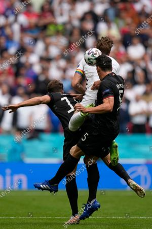 England's Harry Kane, center, jumps for the ball with Germany's Leon Goretzka, left, and Mats Hummels during the Euro 2020 soccer championship round of 16 match between England and Germany at Wembley stadium in London