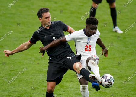 Germany's Mats Hummels, left, duels for the ball with England's Bukayo Saka during the Euro 2020 soccer match round of 16 between England and Germany at Wembley stadium in London
