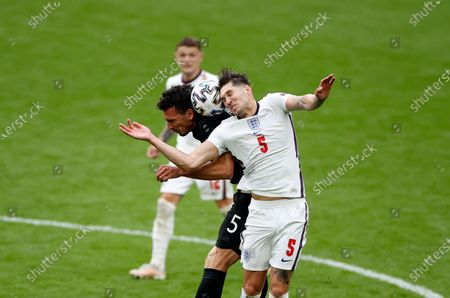 England's John Stones, right, jumps for the ball with Germany's Mats Hummels during the Euro 2020 soccer match round of 16 between England and Germany at Wembley stadium in London