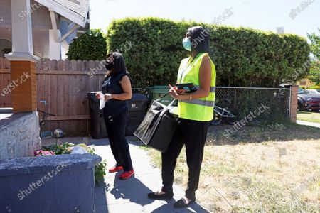 """Lourdes Castro- Ramirez, secretary of business, consumer services and housing agency, left, and Danette Garcia, right, canvas during a """"Get Out the Vaccine"""" canvassing event, to encourage members of the public to receive their COVID-19 vaccinations in South L.A. on Tuesday, June 8, 2021 in Los Angeles, CA. With less than a week to go until the """"Vac for the Win"""" 15 million dollars grand prize drawing, the canvassing effort with Newsom administration officials kicked off the event with a rally at the L.A. Trade Technical College. (Dania Maxwell / Los Angeles Times)"""
