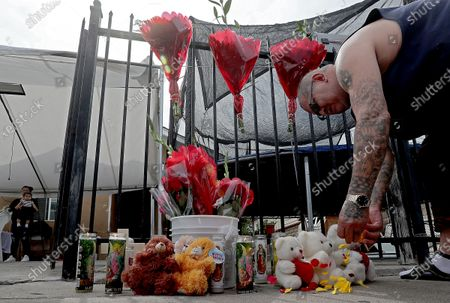 """. Next door neighbor Jose Angel Hernandez, 58, leaves rose petals at a makeshift memorial for three slain children outside the children's home in East Los Angeles on Tuesday, June 29, 2021. Their mother, Sandra Chico, 28, was taken into custody as a """"person of interest"""" after deputies found her children unresponsive in the home Monday afternoon. She was arrested on suspicion of murder and is being held in lieu of $2 million, Los Angeles County sheriff's officials. (Luis Sinco / Los Angeles Times)"""
