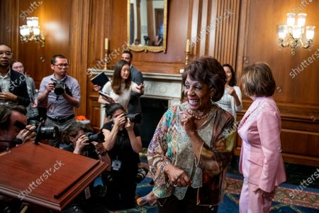 Speaker of the United States House of Representatives Nancy Pelosi (Democrat of California), right, shares a light moment with United States Representative Maxine Waters (Democrat of California), left, after signing three Congressional Review Act Resolutions, S. J. Res. 13, 14 and 15, at the US Capitol in Washington, DC,.