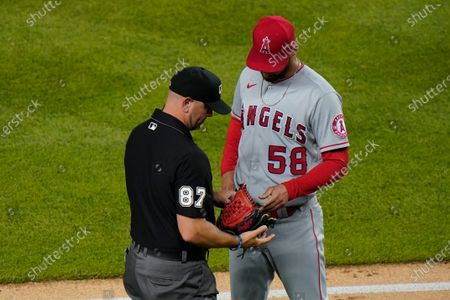 Umpire Scott Barry checks the glove of Los Angeles Angels relief pitcher Alex Claudio (58) during the eighth inning of the team's baseball game against the New York Yankees, in New York. The Yankees won 11-5