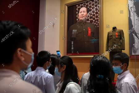 Visitors look at a display showing the suit Chinese leader Mao Zedong was wearing when he declared the establishment of the People's Republic of China at the newly-completed Museum of the Communist Party of China in Beijing, . In the build-up to the July 1 anniversary, Chinese President Xi Jinping and the party have exhorted its members and the nation to remember the early days of struggle in the inland hills of Yan'an, where Mao Zedong emerged as party leader in the 1930s