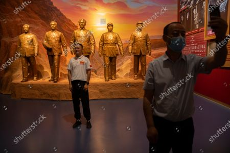 Visitors pose for photos in front of statues of Chinese Leader Mao Zedong, center, and other Communist Party figures at the newly-completed Museum of the Communist Party of China in Beijing, . In the build-up to the July 1 anniversary, Xi and the party have exhorted its members and the nation to remember the early days of struggle in the inland hills of Yan'an, where Mao Zedong emerged as party leader in the 1930s