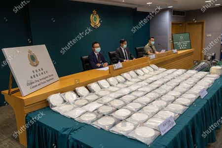 Stock Photo of Divisional Commander (Airport Investigation) of Customs Drug Investigation Bureau, Lau Leung-chi, (L), the Head of Customs Drug Investigation Bureau, Lee Kam-wing, (C), and the Divisional Commander (Air Cargo) of Airport Command, CheungTin-ho, (R), attend a press conference showing seized bags of cocaine at the Customs Headquarters Building in Hong Kong, China, 30 June 2021. On 22 June 2021 Hong Kong Customs inspected an air cargo consignment arriving from Brazil at Hong Kong International Airport and seized about 110 kilograms of suspected cocaine inside two hydraulic devices with an estimated market value of about 130 million HK dollar, about 16.7 million US dollar.