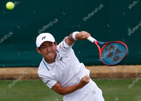 Japan's Yoshihito Nishioka serves to John Isner of the United States during the men's singles first round match on day three of the Wimbledon Tennis Championships in London