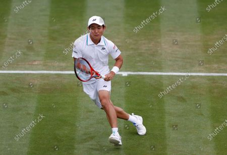 Japan's Yoshihito Nishioka chases to return to John Isner of the United States during the men's singles first round match on day three of the Wimbledon Tennis Championships in London