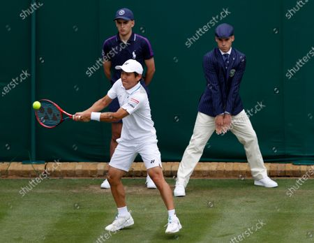 Japan's Yoshihito Nishioka returns to John Isner of the United States during the men's singles first round match on day three of the Wimbledon Tennis Championships in London