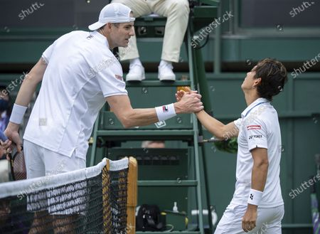 Japan's Yoshihito Nishioka shakes hands with John Isner of the United States after his win during the men's singles first round match on day three of the Wimbledon Tennis Championships in London