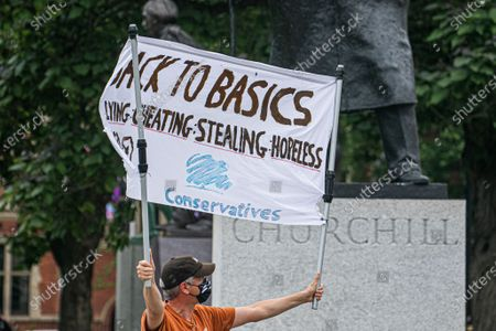 """A lone protester wearing a facemaskholds a banner  in Parliament Square which reads """"Back To Basics, lying, cheating, stealing, hopeless"""" demonstrate  against the sleaze and sex in the Conservative government in the wake of the resgntion of Health secretary Matt Hancock over his affair with an aide Gina Colangelo"""
