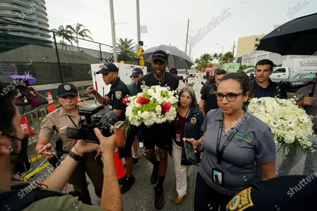 Stock Photo of Miami Heat forward Udonis Haslem, carrying flowers, walks with his arm around Miami-Dade County Mayor Daniella Levine Cava as he arrives to pay his respects at a makeshift memorial to the people who were killed and the scores who remain missing, nearly a week after the partial collapse of the Champlain Towers South condo building, in Surfside, Fla