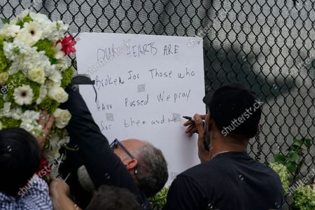 Miami Heat forward Udonis Haslem writes a message on the wall as flowers he brought are affixed beside it, at a makeshift memorial to the people who were killed and the scores who remain missing, nearly a week after the partial collapse of the Champlain Towers South condo building, in Surfside, Fla