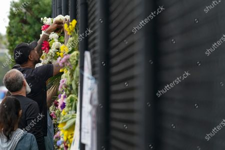 Miami Heat forward Udonis Haslem attaches the flowers he brought to the fence as he pays his respects at a makeshift memorial to the people who were killed and the scores who remain missing, nearly a week after the partial collapse of the Champlain Towers South condo building, in Surfside, Fla
