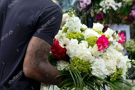 Stock Picture of Miami Heat forward Udonis Haslem carries flowers as he arrives to pay his respects at a makeshift memorial to the people who were killed and the scores who remain missing, nearly a week after the partial collapse of the Champlain Towers South condo building, in Surfside, Fla