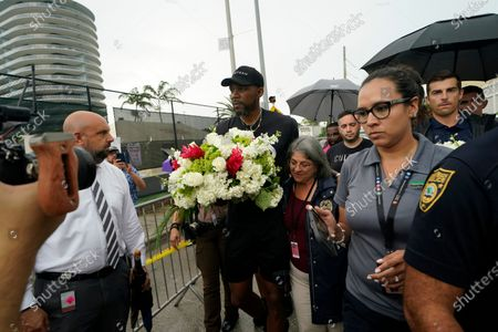 Stock Image of Miami Heat forward Udonis Haslem, carrying flowers, walks with his arm around Miami-Dade County Mayor Daniella Levine Cava as he arrives to pay his respects at a makeshift memorial to the people who were killed and the scores who remain missing, nearly a week after the partial collapse of the Champlain Towers South condo building, in Surfside, Fla