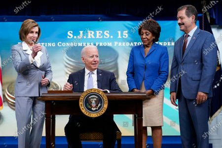 House Speaker Nancy Pelosi of Calif., left, holds a pen after President Joe Biden, second from left, signed one of three bills during an event in the South Court Auditorium on the White House complex in Washington, . They are joined by Rep. Maxine Waters, D-Calif., second from right, and Rep. Chuy Garcia, D-Ill., right