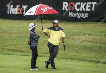 Hideki Matsuyama of Japan (R) talks with manager Ken Hirai (L) while waiting to walk onto the twelfth green during the Pro-am for the Rocket Mortgage Classic golf tournament at the Detroit Golf Club in Detroit, Michigan, USA, 30 June 2021.