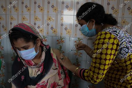 A health worker inoculates a sex worker with the COVAXIN vaccine against the Covid-19 coronavirus during a vaccination drive at A Red Light Area  in Kolkata, India, on June 30, 2021.