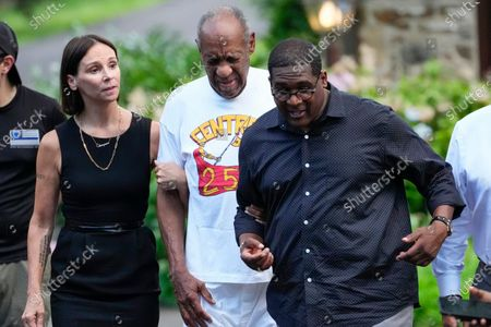 Bill Cosby, center, and spokesperson Andrew Wyatt, right, approach members of the media gathered outside Cosby's home in Elkins Park, Pa., after Pennsylvania's highest court overturned his sex assault conviction