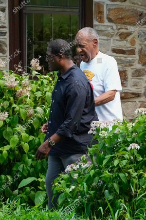 Comedian Bill Cosby, right, and spokesperson Andrew Wyatt walk outside the home of the entertainer in Elkins Park, Pa., . Pennsylvania's highest court has overturned Cosby's sex assault conviction. The court said Wednesday, that they found an agreement with a previous prosecutor prevented him from being charged in the case. The 83-year-old Cosby had served more than two years at the state prison near Philadelphia and was released