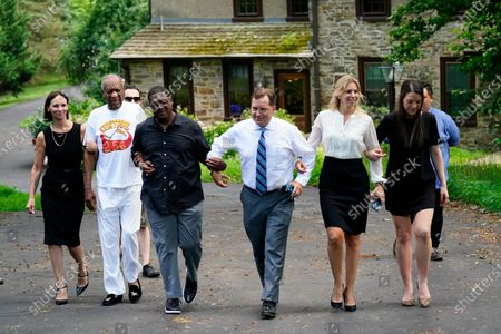 Bill Cosby, second left, and spokesperson Andrew Wyatt, third left, approach members of the media gathered outside Cosby's home in Elkins Park, Pa., after Pennsylvania's highest court overturned his sex assault conviction