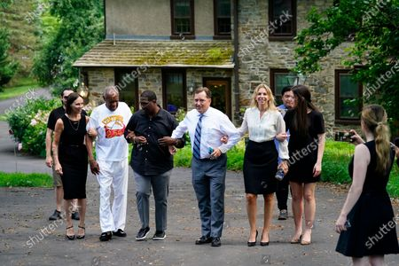 Stock Image of Bill Cosby, second left, and spokesperson Andrew Wyatt, third left, approach members of the media gathered outside Cosby's home in Elkins Park, Pa., after Pennsylvania's highest court overturned his sex assault conviction