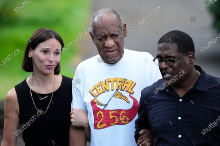Comedian Bill Cosby, center, and spokesperson Andrew Wyatt, right, approach members of the media gathered outside Cosby's home in Elkins Park, Pa., after Pennsylvania's highest court overturned his sex assault conviction