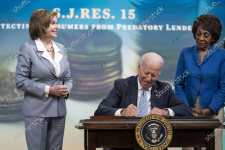 Stock Picture of President Joe Biden signs S.J.Res.15, one of the three Congressional Review Act bills, into law as House Speaker Nancy Pelosi, D-CA, (L), and Rep. Maxine Waters, D-CA, look on, in Washington, DC, on Wednesday, June 30, 2021. The bills aim to reverse Trump era policies related to worker discrimination, methane emissions and the 'True Lender' rule.