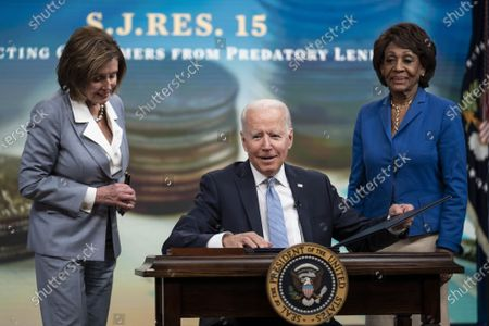 President Joe Biden signs S.J.Res.15, one of the three Congressional Review Act bills, into law as House Speaker Nancy Pelosi, D-CA, (L), and Rep. Maxine Waters, D-CA, look on, in Washington, DC, on Wednesday, June 30, 2021. The bills aim to reverse Trump era policies related to worker discrimination, methane emissions and the 'True Lender' rule.