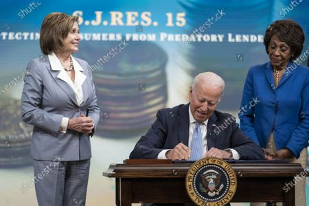 Stock Photo of United States President Joe Biden signs S.J.Res.15, one of the three Congressional Review Act bills, into law in Washington, DC,.The bills aim to reverse Trump era policies related to worker discrimination, methane emissions and the 'True Lender' rule. Looking on at left is Speaker of the US House of Representatives Nancy Pelosi (Democrat of California) and at right is US Representative Maxine Waters (Democrat of California)